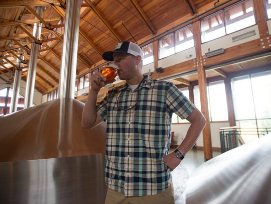 Production Brewmaster Christian Holbrook takes a drink