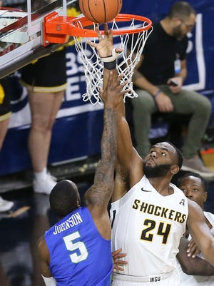 Wichita State center Shaquille Morris tries to block the shot of Florida Gulf Coast guard Zach Johnson, left, during the second half of an NCAA college basketball game Friday, Dec. 22, 2017, in Wichita, Kan. (Travis Heying/The Wichita Eagle via AP)