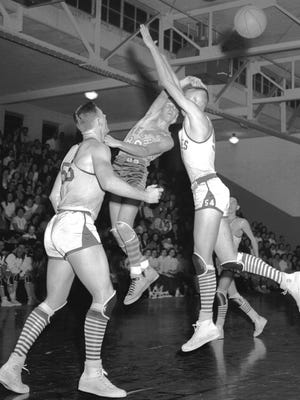 Tech High School's Wayne Smith (center) shoots a hook shot over the head of Treadwell's Don Wynn (right) on Jan. 6, 1953, as Treadwell's Robert Hyde, the game's top scorer with 26 points, watches at left. The Yellowjackets gave Treadwell a real run, but finally fell to the taller Eagles, 78-65.