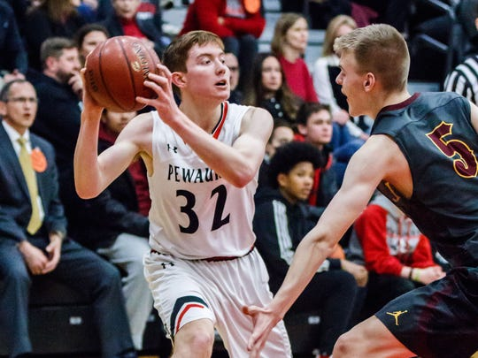 Pewaukee sophomore Gabe Guidinger (32) looks to pass around West Allis Central's Cameron Drury (5) during the game at Pewaukee on Friday, Feb. 02, 2018.
