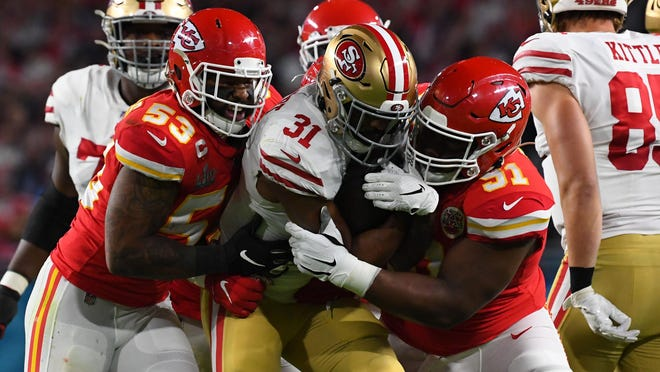 San Francisco 49ers running back Raheem Mostert (31) is tackled by Kansas City Chiefs inside linebacker Anthony Hitchens (53) and nose tackle Derrick Nnadi (91) during the first quarter in Super Bowl LIV at Hard Rock Stadium.