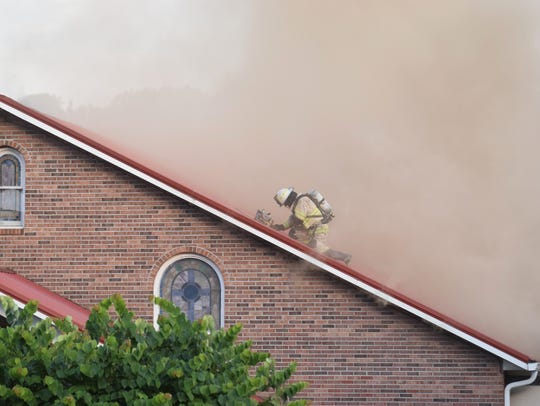 A Knoxville firefighter climbs on top of a roof amid
