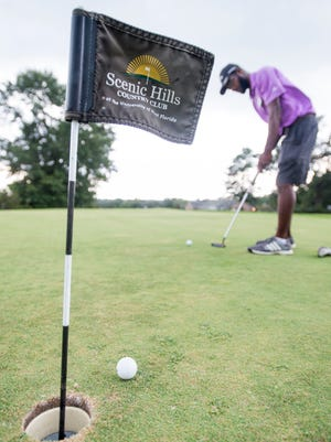 The First Tee of Northwest Florida coach Devin Collins putts on the practice green at the Scenic Hills Country Club at the University of West Florida in Pensacola on Monday, Aug. 14, 2017.  UWF is selling the course to RNL Investment Group LLC.
