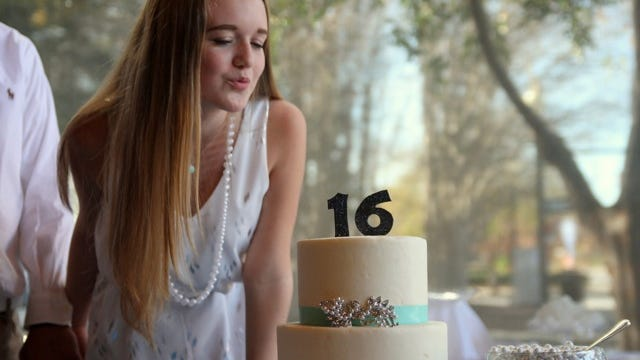Rebecca Neal blows out the candles on her Sweet 16 birthday cake.
