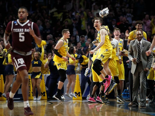 Michigan guard Duncan Robinson, center right, jumps as he and teammates celebrate during the second half of an NCAA men's college basketball tournament regional semifinal against Texas A&M on Thursday, March 22, 2018, in Los Angeles. (AP Photo/Jae Hong)