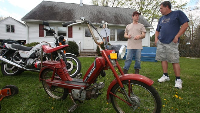 Tony Delia, left, shows Freddy Franco of Haverstraw a moped on display during a yard sale at his Blauvelt home during the Western Highway Roundup community sale on May 3. The event was organized by the Blauvelt Library.