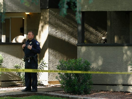 A Phoenix police officer stands guard in front of an apartment building as authorities search an apartment Monday, May 4, 2015, in Phoenix, believed to be the home of one of the gunmen, who was shot and killed the night before in suburban Dallas outside a suburban Dallas venue hosting a provocative contest for Prophet Muhammad cartoons. (AP Photo/Ross D. Franklin)