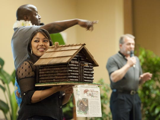 """Maria Hernandez holds """"Un-Corked"""" by John Murray, one of eight birdhouses in the live auction, as Paul Gittens and Flint Epps acknowledge bids during Habitat for Humanity's eighth annual Birdhouse Auction at the Holiday Inn on Friday, May 3, 2013."""