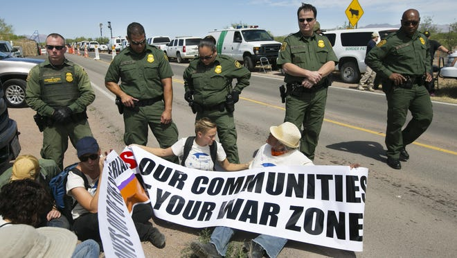 """David Wallace/The RepublicArivaca residents have been campaigning for the removal of the Arivaca Road checkpoint for the past two years. Protestors Sophie Smith (left in blue hat) of Arivaca, Geena Jackson (center) of Tucson and Jolene Montana (right) of Arivaca, sit down along the side of Arivaca Road, behind the """"no authorized entry area"""" in front of Border Patrol Agents blocking their way at the Border Patrol checkpoint on Arivaca Road in Amado, Ariz., on Wednesday, May 27, 2015. Around 75 protestors rallied to have the checkpoint shut down."""