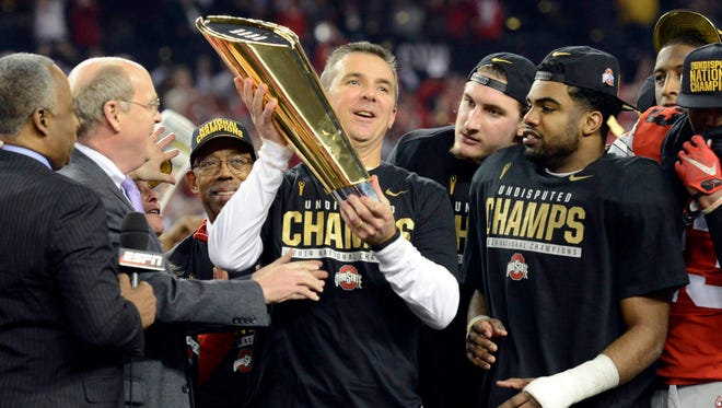 Ohio State coach Urban Meyer celebrates with the championship trophy after the Buckeyes beat Oregon to win the 2014 national title.