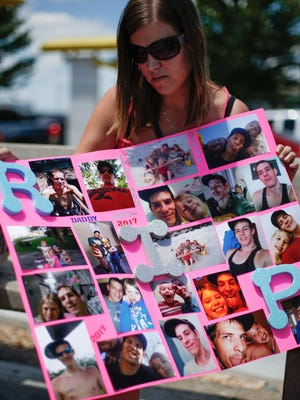 A collage of photos of Adam Hilburn is held by Stefanie Cobb, the mother of his three daughters, on Friday, June 9, 2017. Hilburn was shot and killed in a Springfield parking lot on Wednesday.
