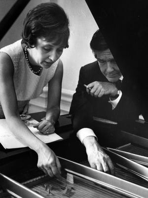 John Cage, composer-in-residence at UC in 1967, helps pianist Jeanne Kirstein add bolts, pennies and cardboard to the piano strings in preparation to performing one of his uncaged works.