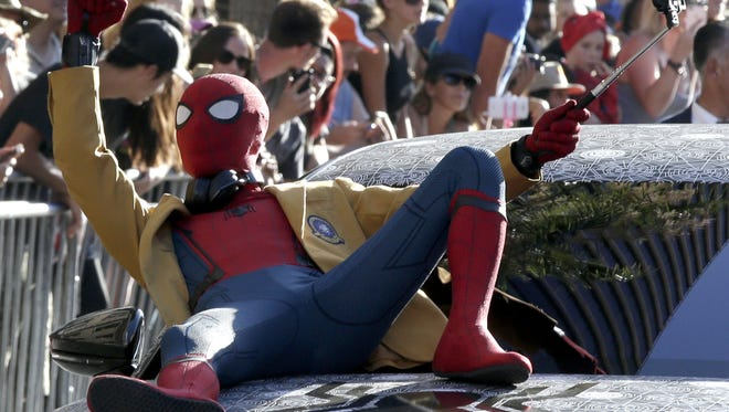 Hey, Spidey! A Spider-Man impersonator (actor Tom Holland arrived in a different kind of suit) shows up at the 'Spider-Man' premiere.