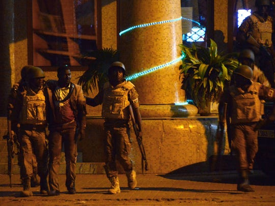 Burkina Faso's soldiers evacuate an injured man from