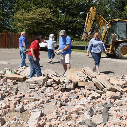 A backhoe leaves the scene Tuesday after dumping a