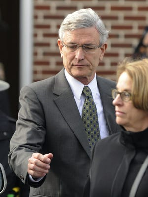 Former Penn State athletic director Tim Curley, center, exits District Court following his arraignment in Harrisburg, Pa.
