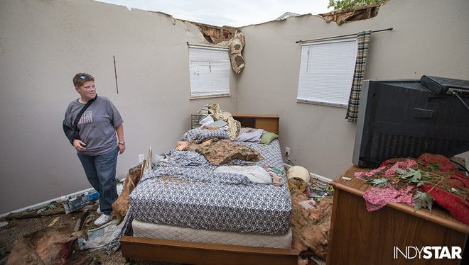 Lisa Skidmore surveys damage to her grandmother's house after a Kokomo tornado swept through. Minor injuries here