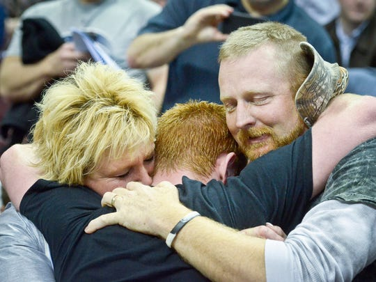 Chance Marsteller of Kennard Dale hugs his parents Suzanne and Darrell after winning the PIAA Class AAA gold medal 170-pound match, Saturday March 8, 2014 at the Giant Center in Hershey. John A. Pavoncello photo