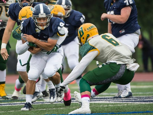 Lebanon Valley College's Brendon Irving is hit from behind by Delaware Valley's TJ Waters and braces for more contact from the Aggies' Jarren McBryde.