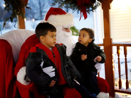 Brothers Adrian Rijo, 5, left, and Kaiden, 2, of Horseheads, each ask Santa for remote control cars at the Big Flats Winter Festival on Dec. 17.