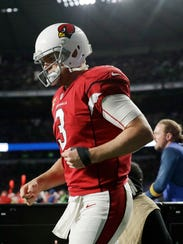 Cardinals quarterback Carson Palmer leaves the field after breaking his left arm during Sunday's game against the Rams in London.