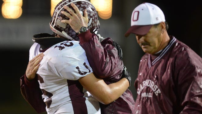 Tucker Lowery and Owen football coach Kenny Ford embrace after the Warhorses' win at Polk County on Oct. 31.