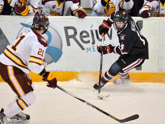 St. Cloud State's Patrick Newell (14) looks for a way past Minnesota-Duluth's Carson Soucy (21) in the first period Friday night at the Herb Brooks National Hockey Center in St. Cloud.