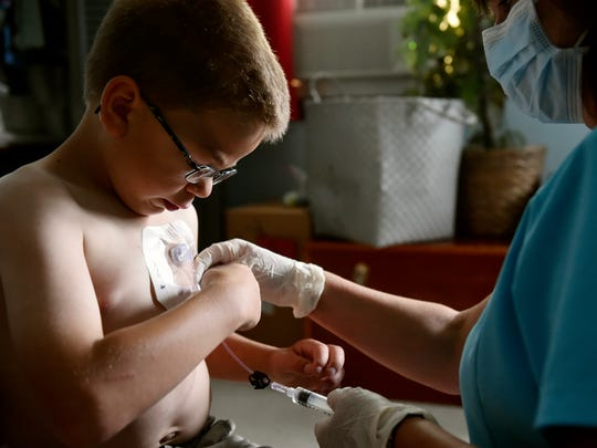 SpiriTrust Lutheran nurse Susan McElwee, right, seals a patch to hold in place a tube for Sean Kisielnicki's weekly enzyme replacement infusion in his Hopewell Township bedroom Wednesday, July 12, 2017. The Kisielnicki family, whose children range in age from 5 to 15, have structured their lives around caring for Sean, whose high-energy presence requires constant supervision and who receives weekly in-home enzyme replacement therapies.