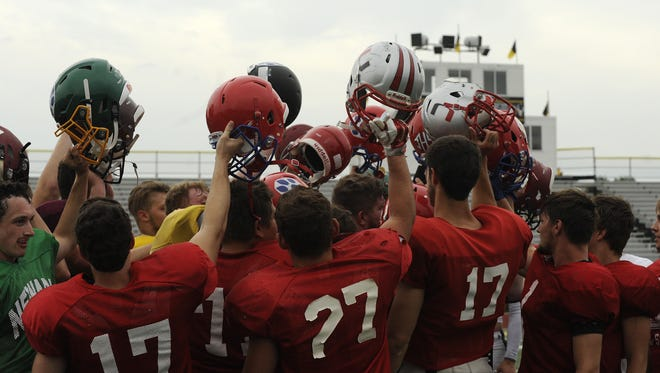 The Licking County all-star football team huddles after practice on Monday at Watkins Memorial High School.