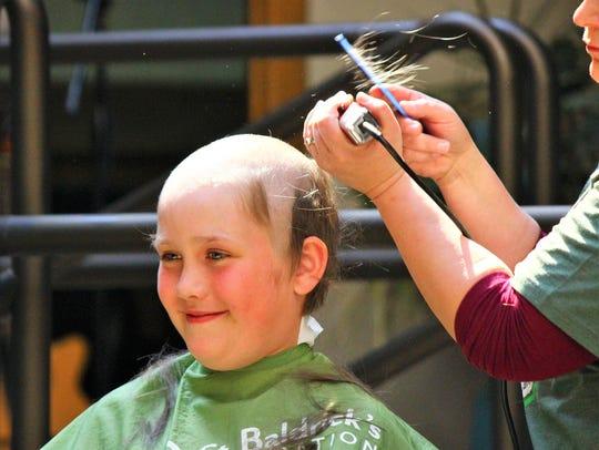 A participant sacrifices their hair for a good cause