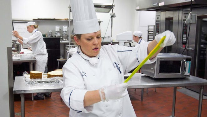 Chef instructor Tracy DeWitt makes a ribbon for the Old West Meets New West cake for Scottsdale's 60th anniversary at Le Cordon Bleu College of Culinary Arts in Scottsdale.