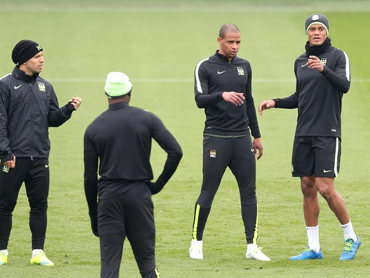 Manchester City's Sergio Aguero, left,  Fernando, second right, and Vincent Kompany, right, attend a training session at the City Football Academy, Manchester, England, Monday April 11, 2016. (Martin Rickett/PA via AP) UNITED KINGDOM OUT