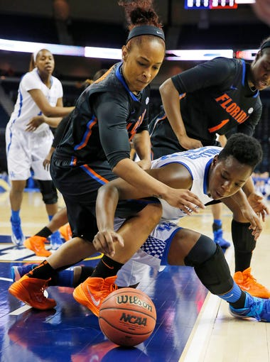 Florida guard Cassie Peoples (13) and Kentucky forward/center Samarie Walker (23) fight for a loose ball in the first half of a quarterfinal women's Southeastern Conference tournament NCAA college basketball game Friday, March 7, 2014, in Duluth, Ga.   (AP Photo/John Bazemore)