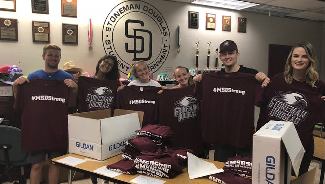 Students pose with their school t-shirts before packaging them up to ship to customers around the world.