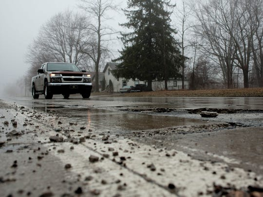 Vehicles pass by large potholes Thursday on M-46 in