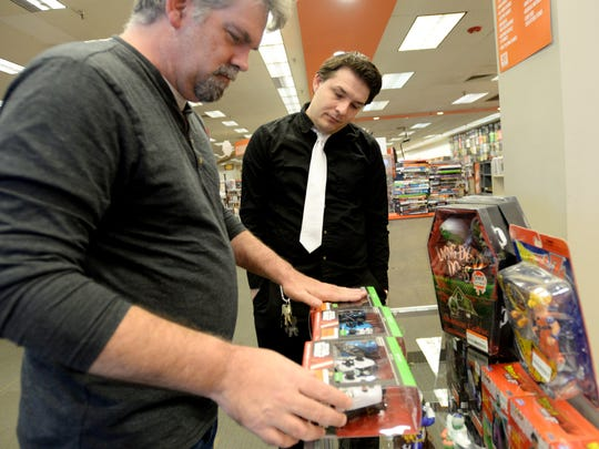 Manager of 2nd & Charles Daniel Savage helps Mike Trichell at the bookstore in Bossier City.