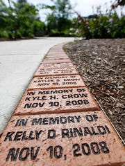 Bricks with the names of those who have died line the