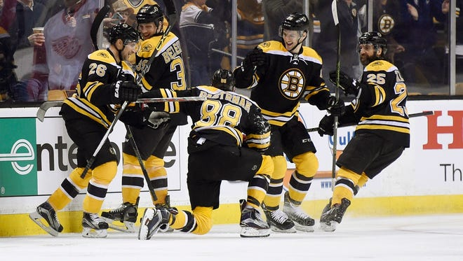 Boston Bruins left wing David Pastrnak (88) celebrates his goal with his teammates during the first period against the Detroit Red Wings at TD Garden.