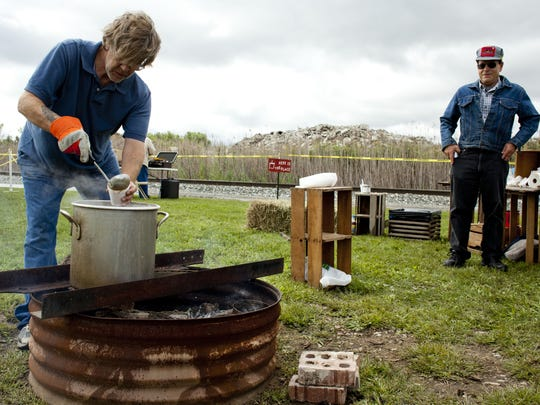 Mark Matts, of Port Huron, serves stew for Bob Winkel, of Rochester, during the 2014 Hobo Fest.