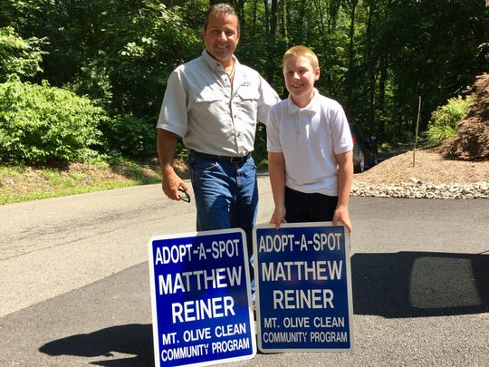 Mount Olive official Mike Pocquat delivers 9-year-old Matthew Reiner his signs.
