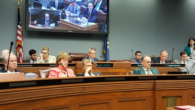 The joint legislative Committee on the Budget members hear testimony Thursday from the State Office of Planning and Budget (on screen in background).  The committee was told the financial shortfall for the current fiscal year would hit $70 million.