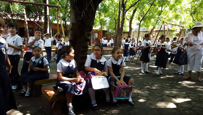 Three little girls enjoy their midmorning snack in a courtyard at Maria Luisa de Marillac School.