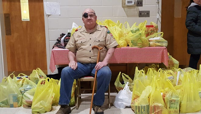Scout Master Bob Shea sits with collected food donations for the Matawan Food Pantry.