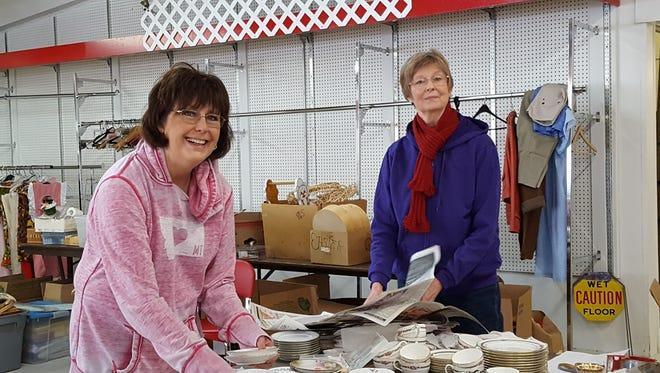 Karen Leeper and Sue Welliver sorting china.