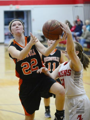 Manitowoc Lutheran's Abby Hiller (32) fouls on Reedsville's Brenna Kiekhaefer (22) while she is attempting a layup during the first half of the game on Friday.