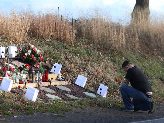 People paid respects to the memory of West Webster volunteer firefighters Michael Chiapperini and Tomasz Kaczowka who were shot and killed when responding to an intentionally set fire in 2012.  A man pulled up to the memorial Thursday, Dec. 24, 2015, got out of his car, kneeled and prayed and then left shortly afterward.