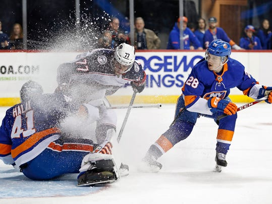 Columbus Blue Jackets right wing Josh Anderson (77) skates into New York Islanders goaltender Jaroslav Halak (41) of Slovakia as Islanders defenseman Sebastian Aho (28) of Sweden watches during the first period of an NHL hockey game in New York, Tuesday, Feb. 13, 2018. (AP Photo/Kathy Willens)
