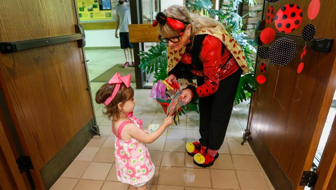 Joyce Tolliver gives an activity to Olivia Williamson, 2, to take home after  Storytime with Ms. Ladybug at the Springfield Conservation Nature Center on Wednesday, May 9, 2018. Tolliver is celebrating her 15th year as Ms. Ladybug.