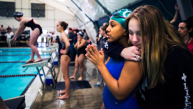 Briarcrest Christian High School freshman Ayanna King, 15, left, receives a hug from St. Agnes Academy freshman Anna Kate Romer, 14, before  competing in the last leg of the 400 freestyle relay during prelims at the Shelby County Swimming Championship at St. George's Independent School's Compton Aquatic Center on Saturday morning.