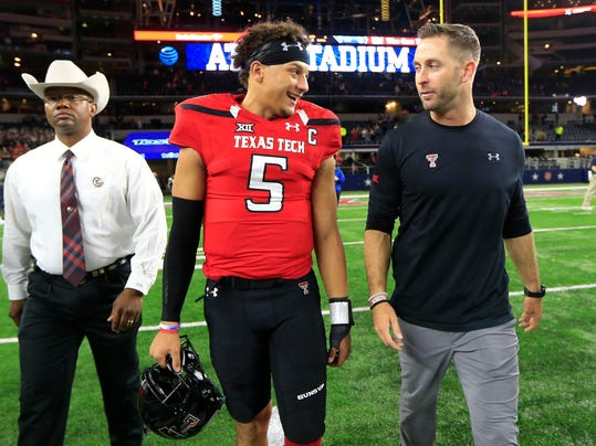 Texas Tech quarterback Patrick Mahomes II, center, and Tech head coach Kliff Kingsbury, right, walk off the playing field defeating Baylor in an NCAA college football game Friday, Nov. 25, 2016, in Arlington, Texas. (AP Photo/Ron Jenkins)